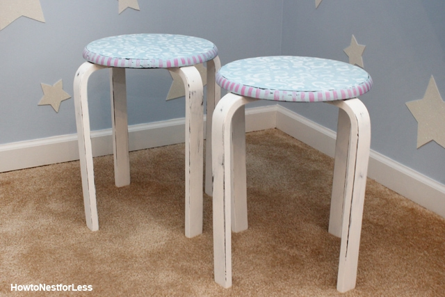 Stenciled blue and pink stools on a rug in a bedroom.