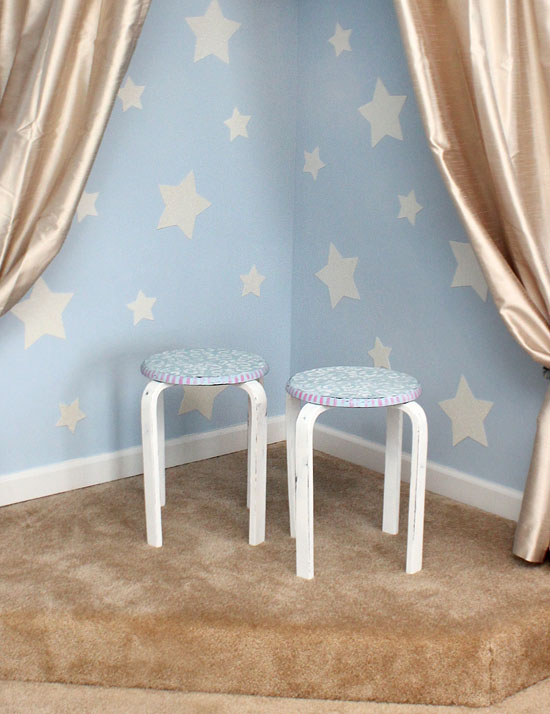 The distressed stenciled stools in front of a star wall and gold curtains.