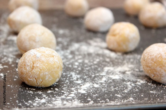 Rolling the dough into balls on a cookie sheet.