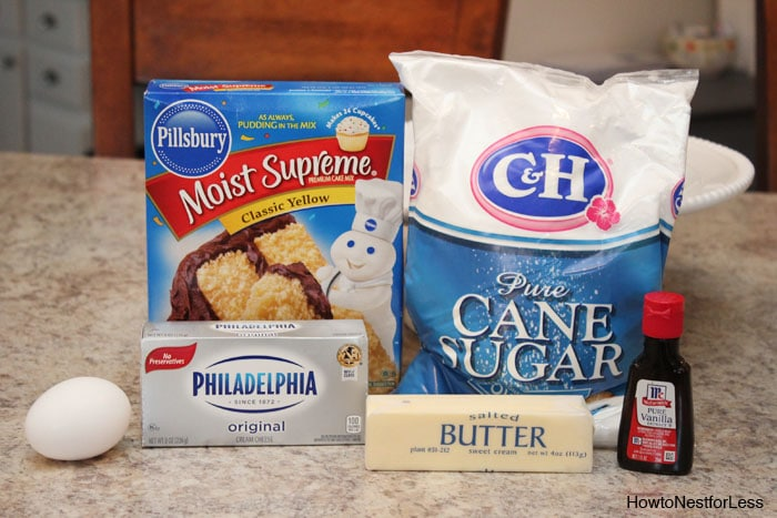 The cane sugar, cream cheese, cake mix and egg, butter and vanilla on the counter.