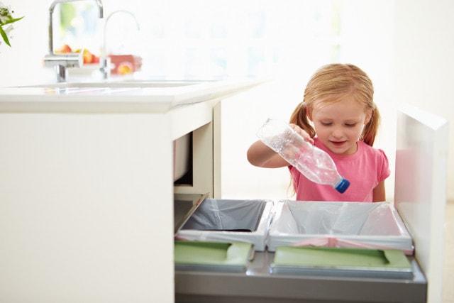 Girl Recycling Kitchen Waste In Bin