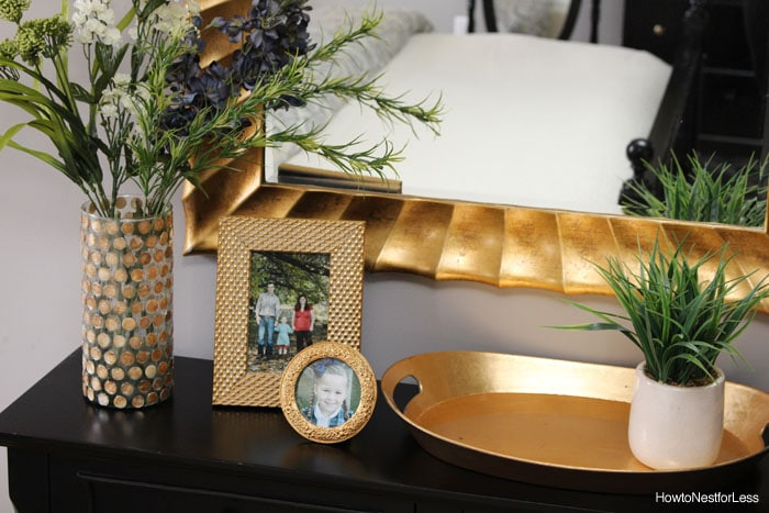 Pictures and gold tray on top of dresser.