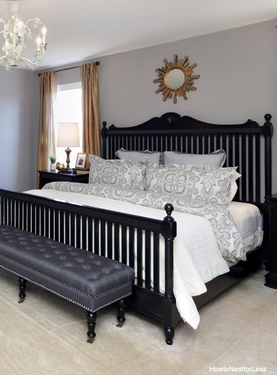 Black bed frame with white bedding and mirror over bed.