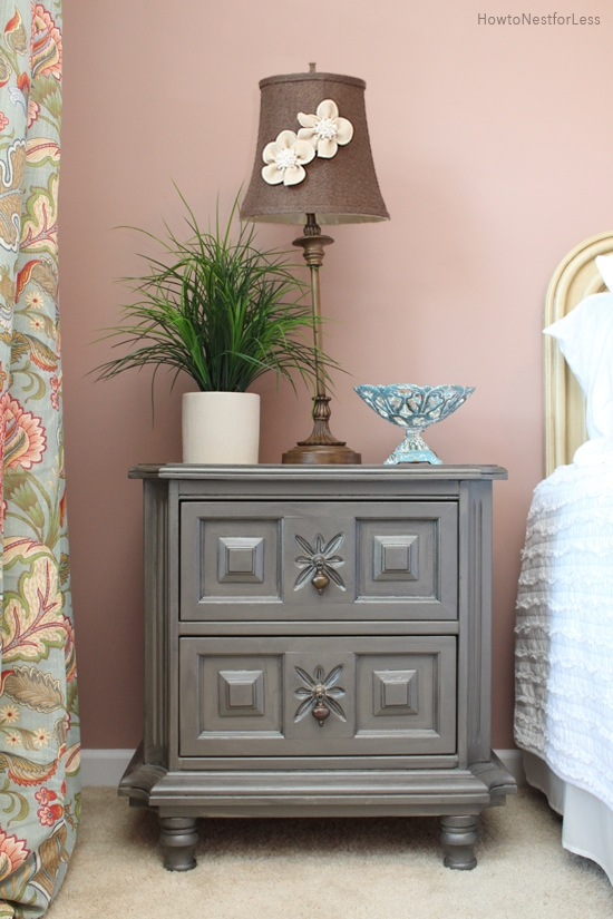 A gray nightstand beside the bed with a lamp, bowl and potted plant on it.