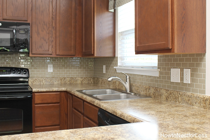 Dark wood kitchen with cream colored tiles.