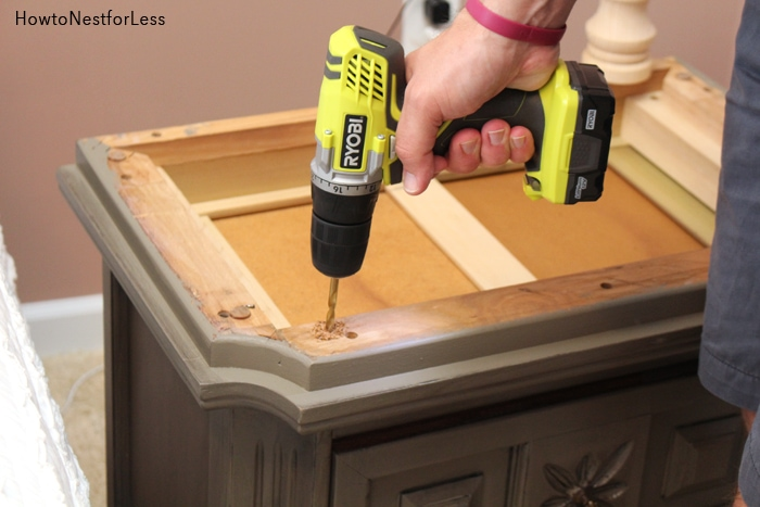 Drilling a screw hole into the night stand.