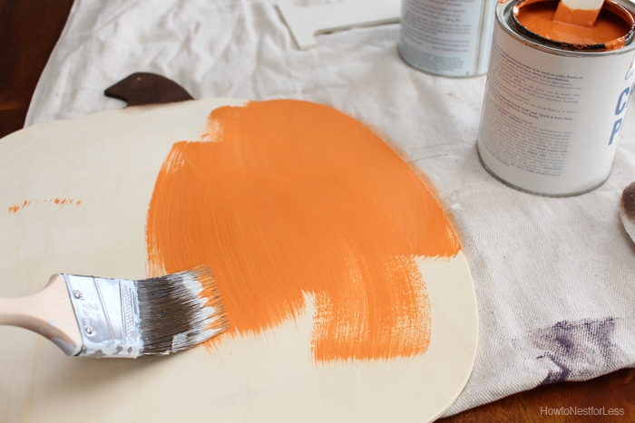Painting the pumpkin orange.