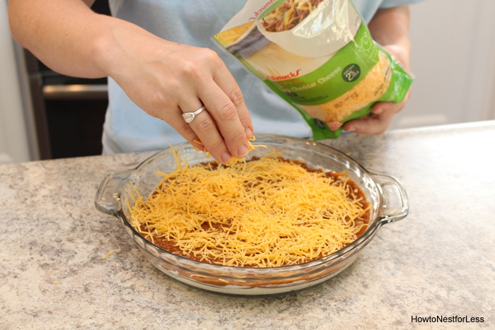 Sprinkling the shredded cheese over the beans.