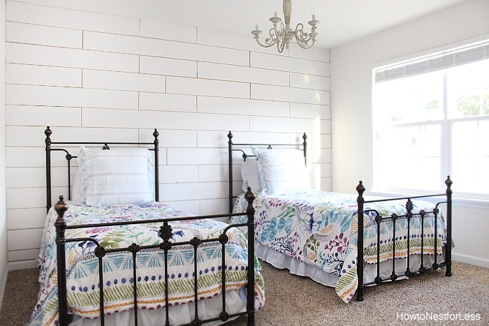 Two wrought iron beds in front of white planked wall.