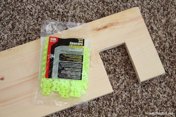 A bag full of spacers on the floor with a plank.