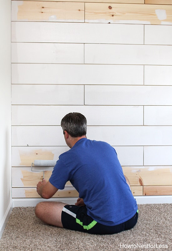 Painting the planked wall white.