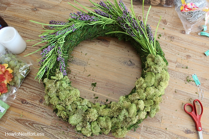 Adding the dried flowers and acorns to the mossy wreath sitting on the desk.
