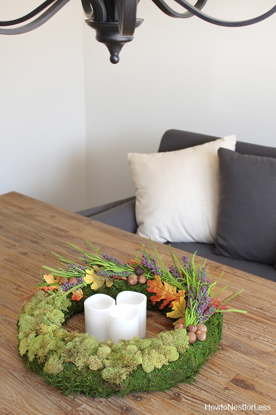 Candles inside the circle of the wreath with a grey couch in the background.