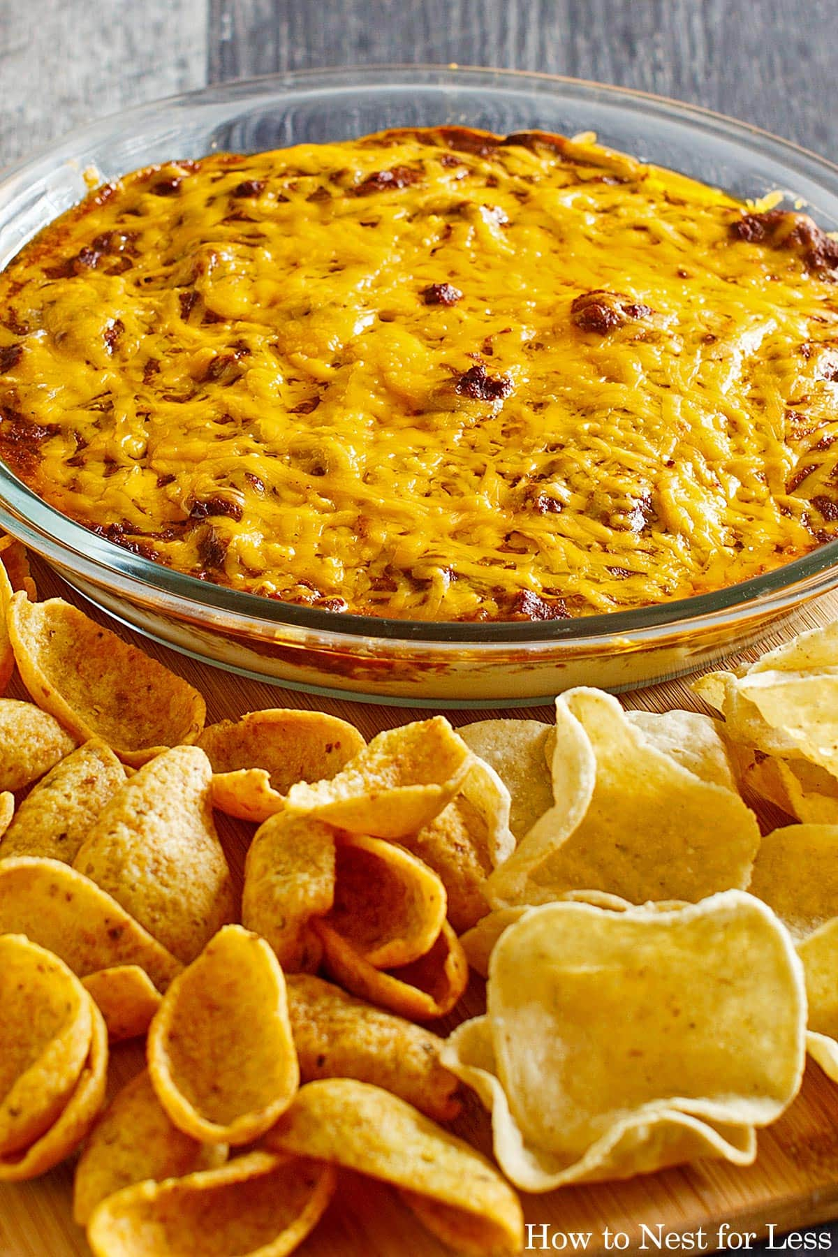 The baked chili dip on counter with chips.