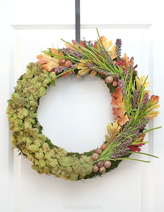 The moss centrepiece and wreath hanging on a door.