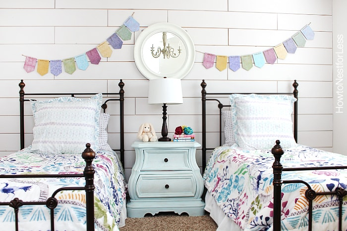 White plank wall girls bedroom with a banner on the wall.
