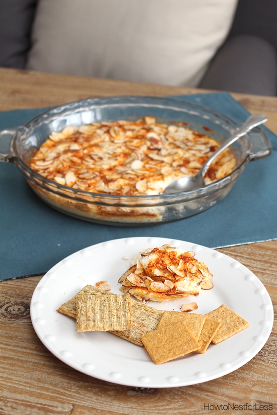 The baked crab dip on the counter, with a white plate beside it and some dip and crackers on it.