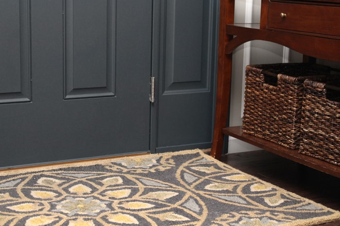 A close up of the rug and painted gray front door.