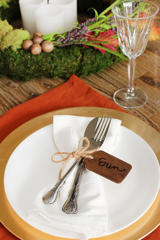 The wooden tag with twine around a knife and fork on the plate.