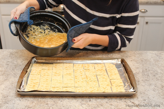 The saltines on the cookie sheet and toffee being poured over them.