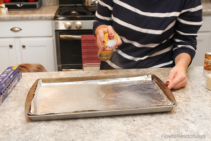 Spraying the cookie sheet with Pam.