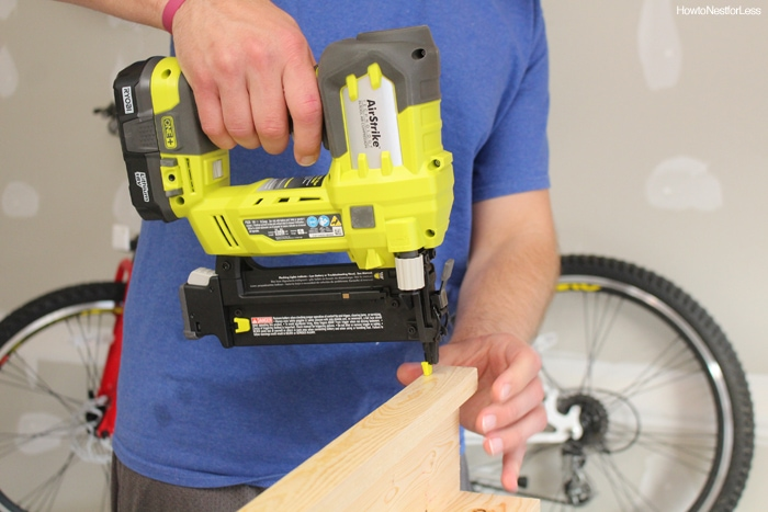 A man holding an electric nail gun on the wood.