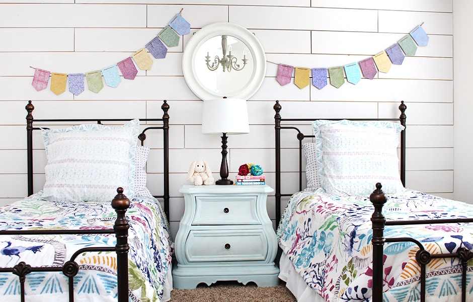 A child's bedroom with shiplap walls and wrought iron beds.