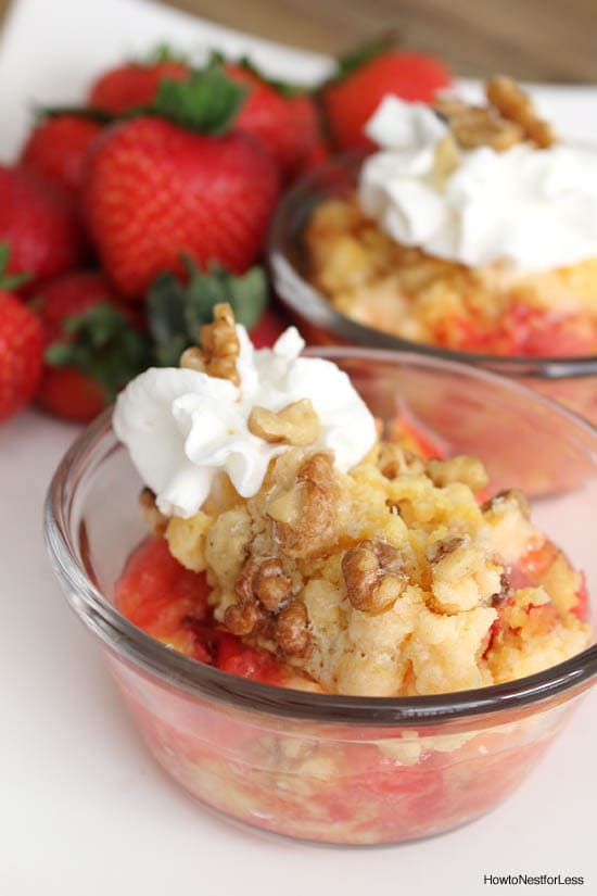 The strawberry pineapple dump cake in a bowl with whip cream on top.