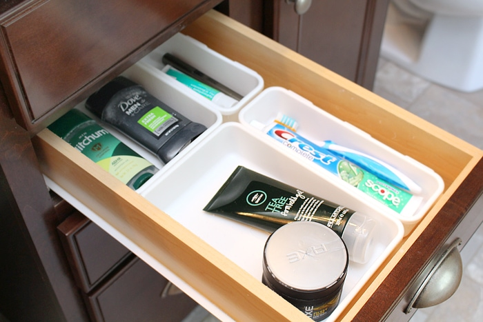 Deodorant, toothbrush and hair products in drawer.