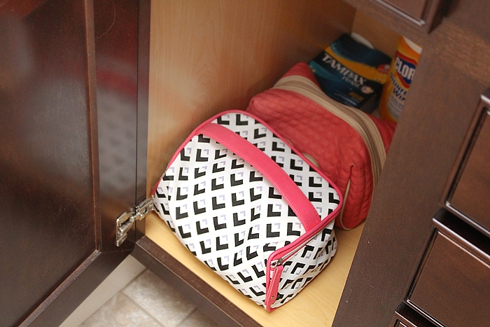 Makeup bags, cleaning supplies and feminine products in cabinet.