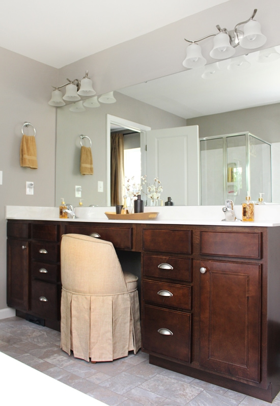 The master bathroom with a large mirror and light fixture above it.