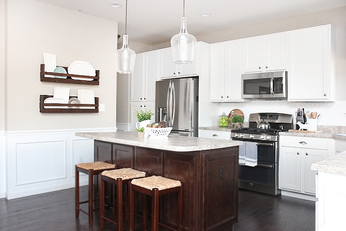 The white kitchen with stainless steel appliances and a wooden rack on the wall.