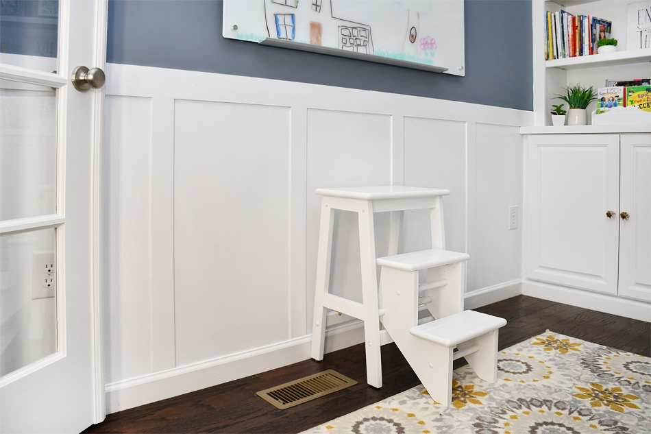 White boards with a gray blue painted wall and a small step stool in front of the boards.