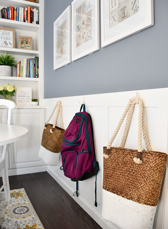 Hooks on the wall with a backpack and bags on the hooks.