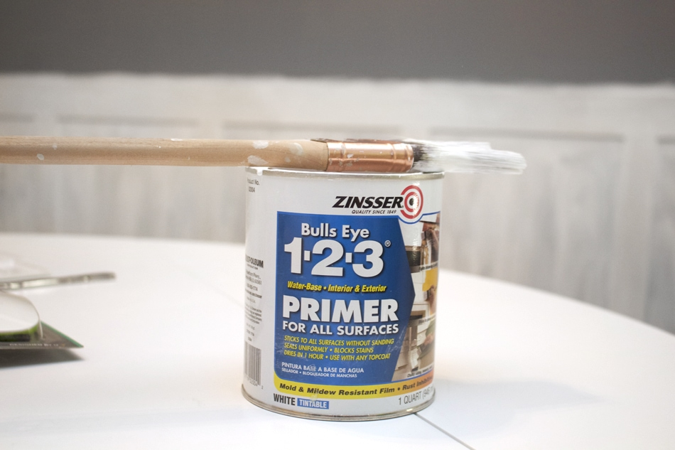 Primer can on the table with a paint brush on top of it.