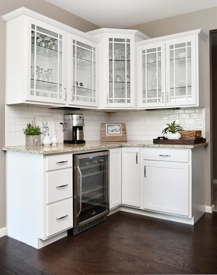 A side cabinet with clear glass and wine glasses inside plus a wine fridge.