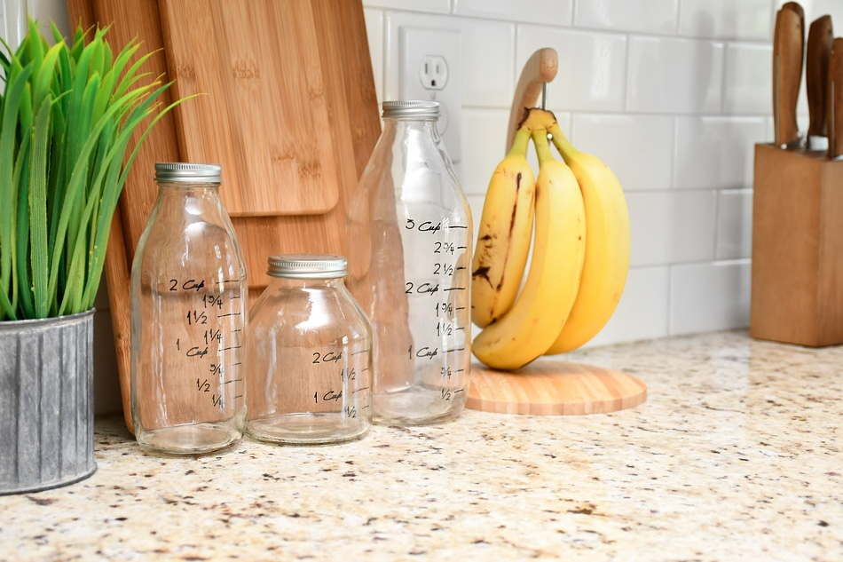 Close up of the white subway tile plus bananas and knives on the counter.
