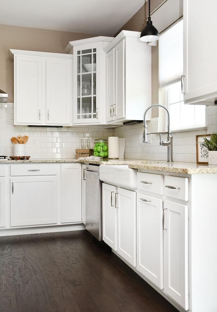 White corner kitchen cabinet with a glass door.
