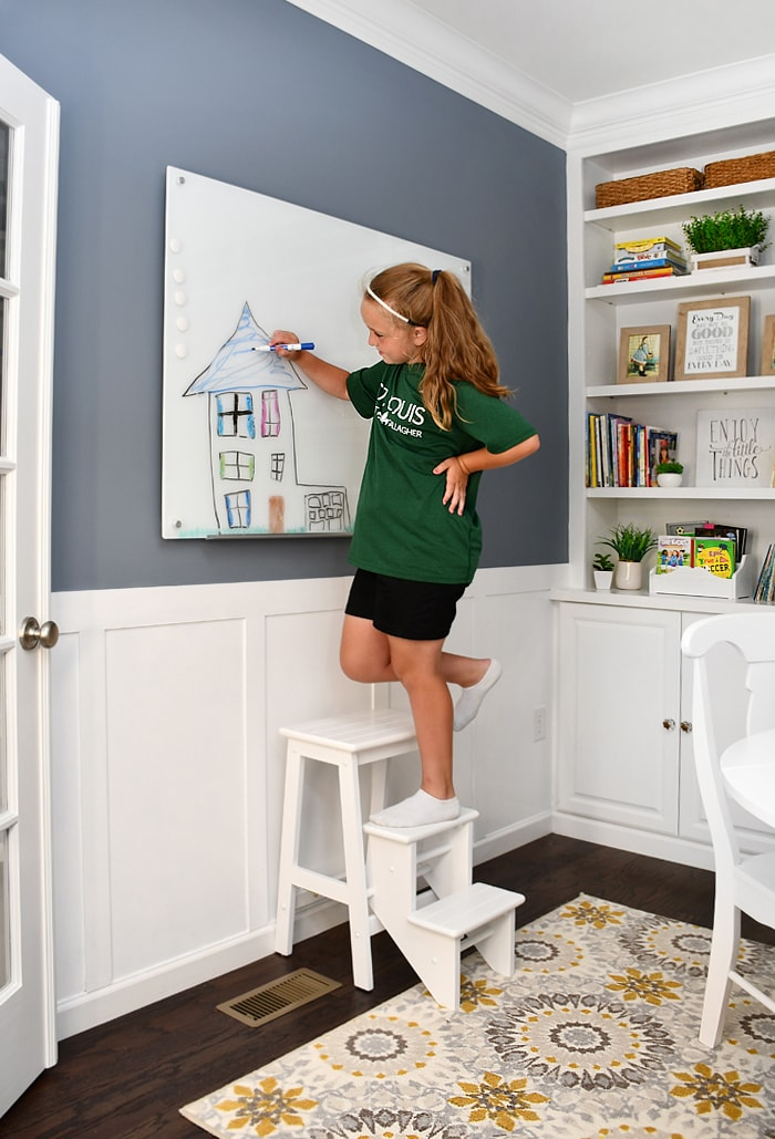 A preteen girl drawing a picture on the wall while standing on a step stool.