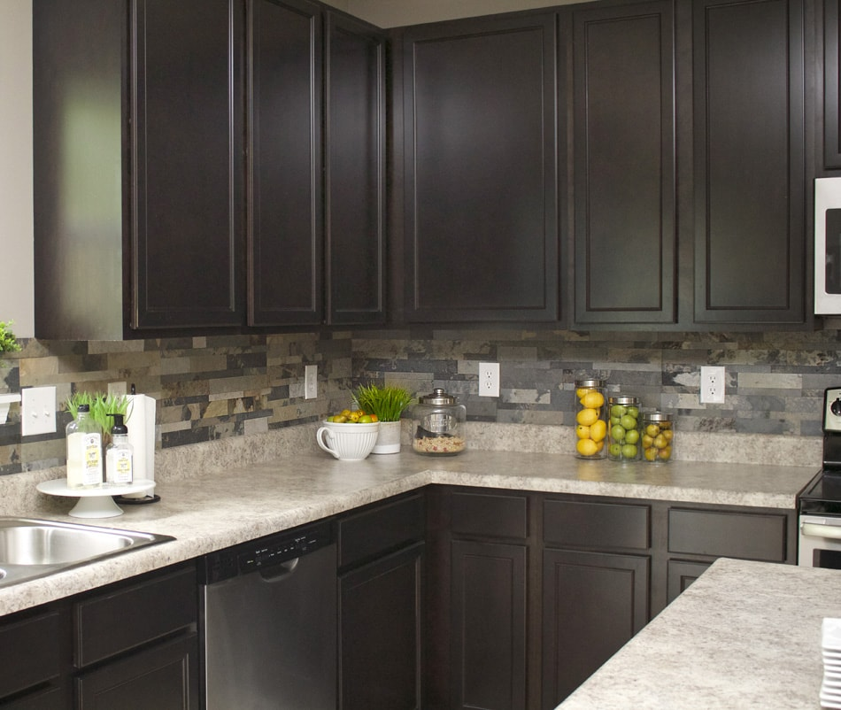 The multicoloured of grey, beige, white faux stone in kitchen with dark cabinets.