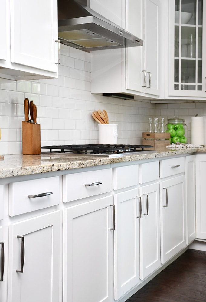 White lower kitchen cabinets with stainless steel pulls.