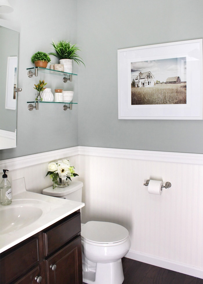 A small bathroom with a picture on the wall.