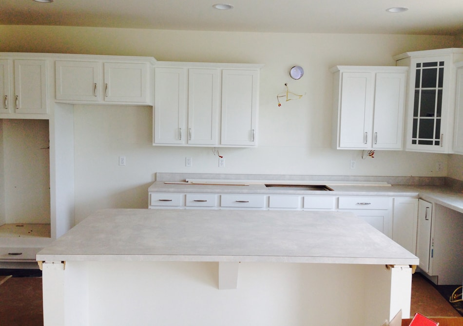 A plain white kitchen with empty shelves and island.
