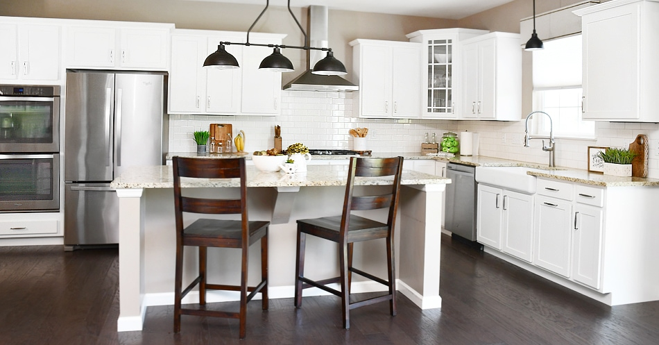 A white kitchen island with two brown wooden chairs at the kitchen island and lights above it.