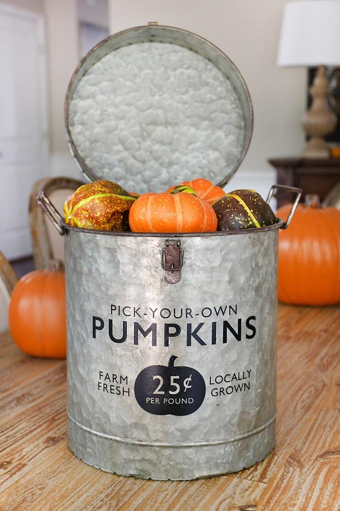 Galvanized bucket filled with pumpkins.