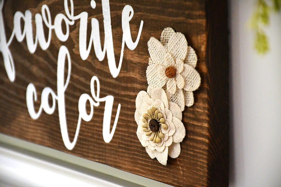 Putting little beige fabric flowers on the wood sign.
