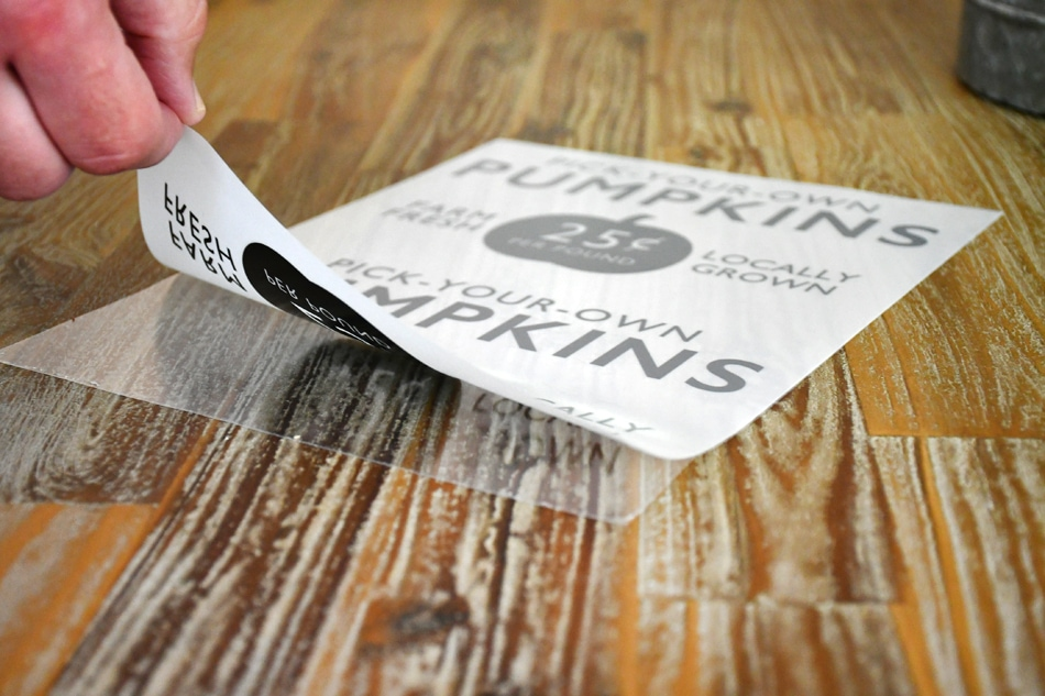 Close up of a hand peeling the sticker back.