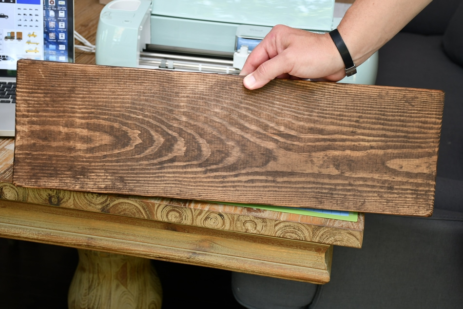 Holding the stained wood upright on a table.