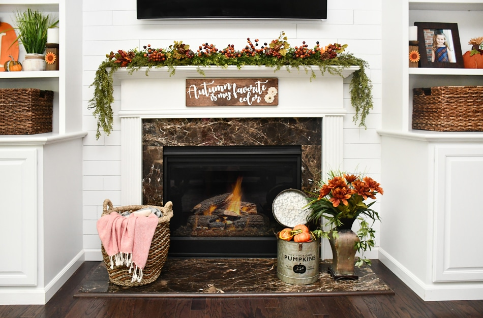 White fireplace mantel with greenery on top and wood diy sign hanging above it.