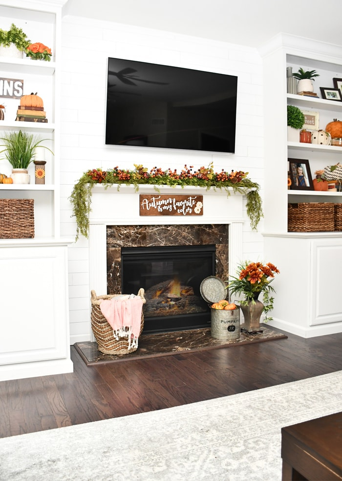 Flowers in large vase in front of fireplace.